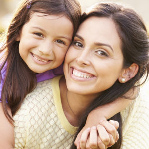 Portrait Of Hispanic Mother And Daughter In Park